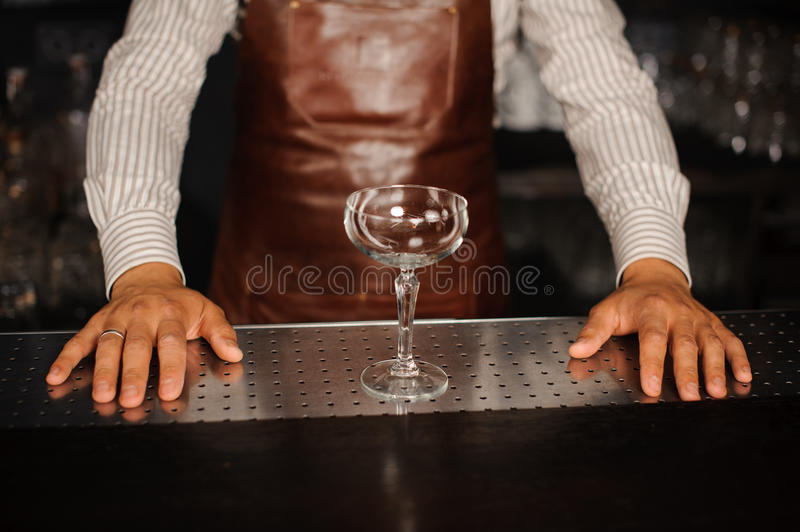 Verre de cocktail d'Ampty devant le barkeeper images stock