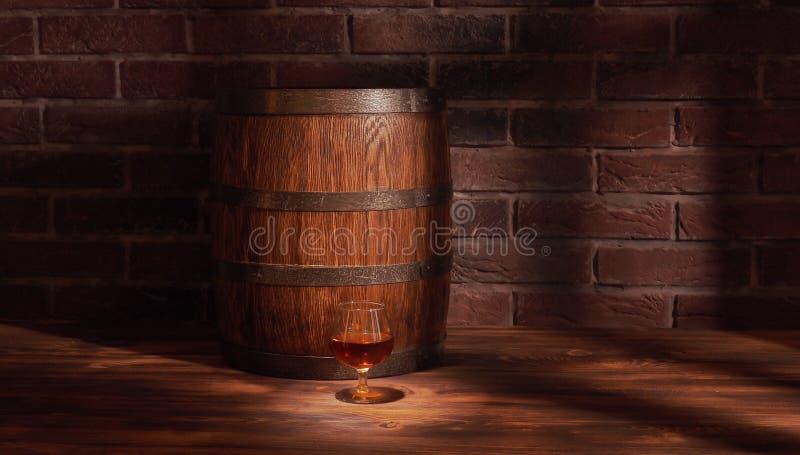 Verre de cognac avec le baril sur la table en bois photo stock