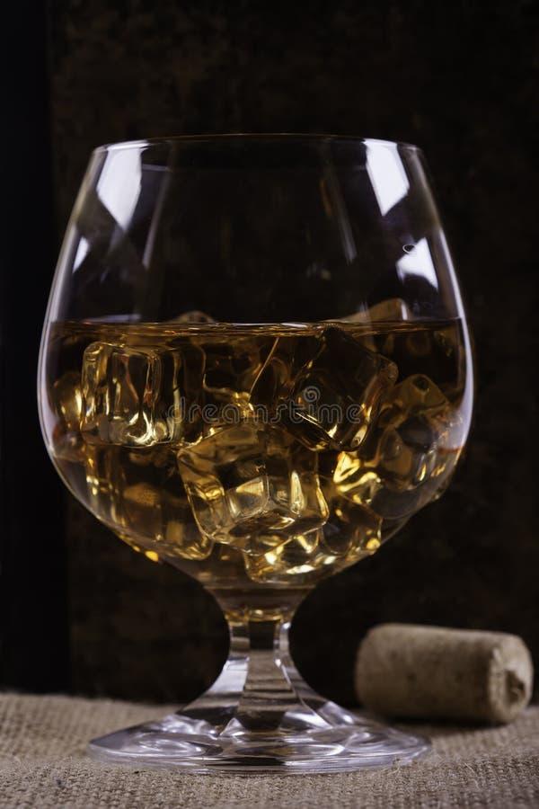 Verre de cognac avec le fond de plan rapproché de glace images stock