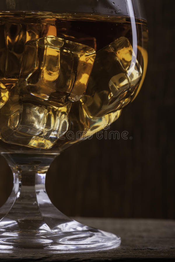 Verre de cognac avec le plan rapproché de glace sur le fond de tissu images libres de droits