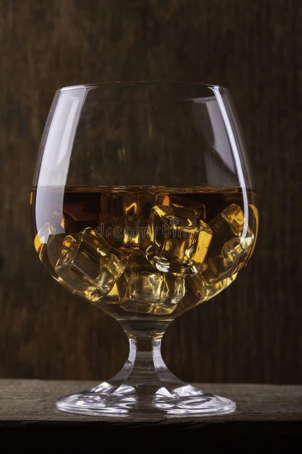Verre de cognac avec le plan rapproché de glace sur le fond de tissu image libre de droits