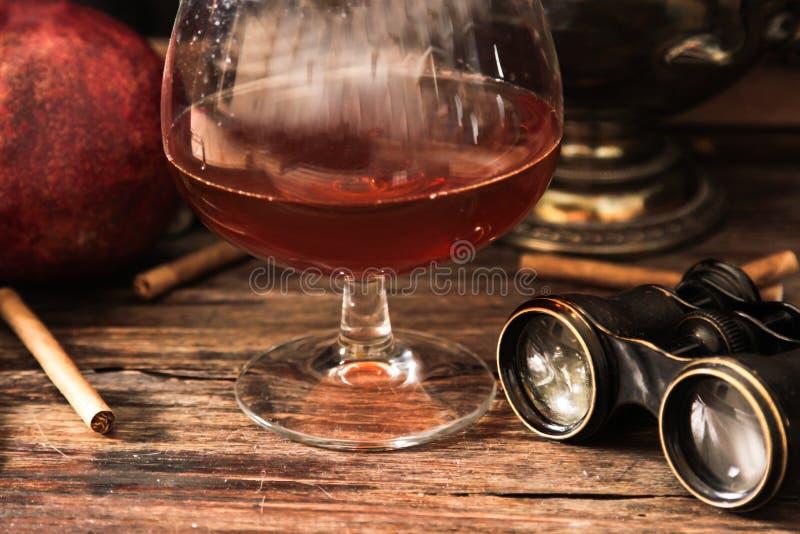 verre de cognac avec les jumelles et la bougie bleue de verre coloré images stock