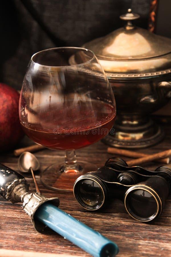 verre de cognac avec les jumelles et la bougie bleue de verre coloré photo stock