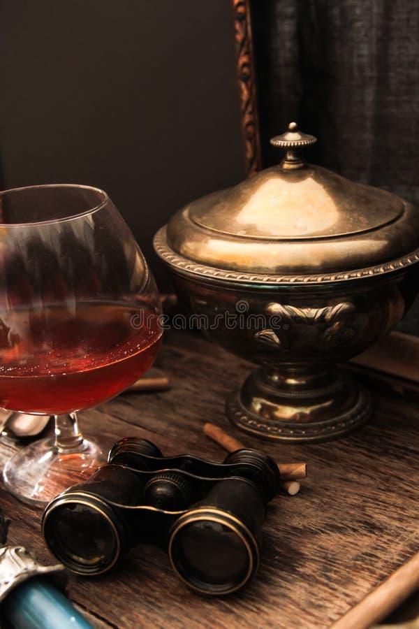 verre de cognac avec les jumelles et la bougie bleue de verre coloré images libres de droits