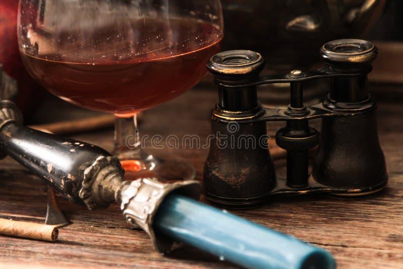 verre de cognac avec les jumelles et la bougie bleue de verre coloré photographie stock