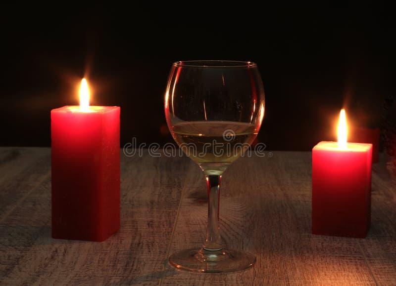 Verre de cognac et de bougie rouge sur un fond en bois images libres de droits