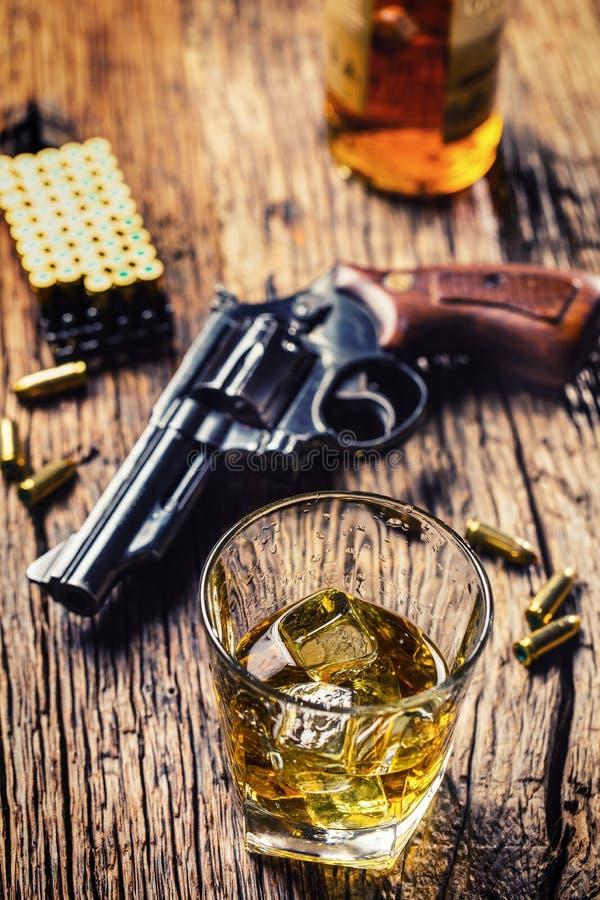 Verre de cognac ou de bourbon de whiskey avec le revolver et les balles dessus images libres de droits