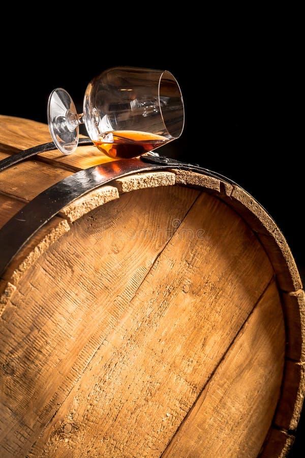 Verre de cognac sur le vieux baril en bois photos stock