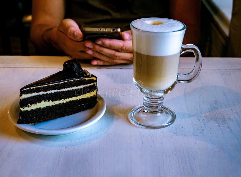 Verre de gâteau de latte et de chocolat sur la table dans un café photo libre de droits