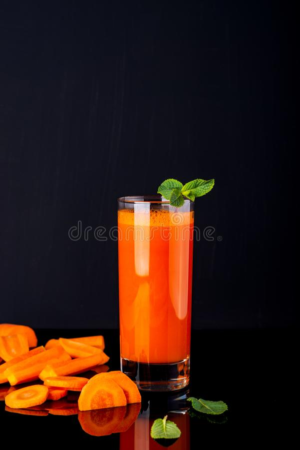 Verre de jus avec des quelques morceaux de carotte sur un fond noir Carotte Juice Drink photos libres de droits