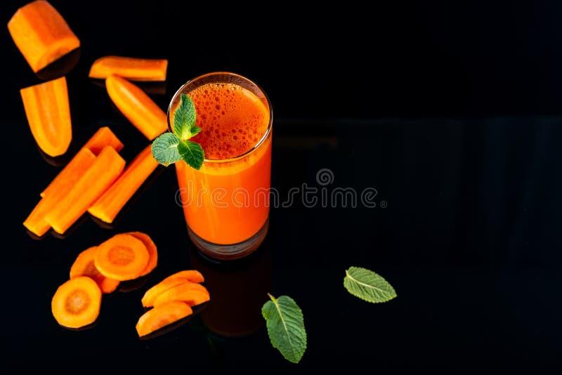 Verre de jus avec des quelques morceaux de carotte sur un fond noir Carotte Juice Drink photos stock