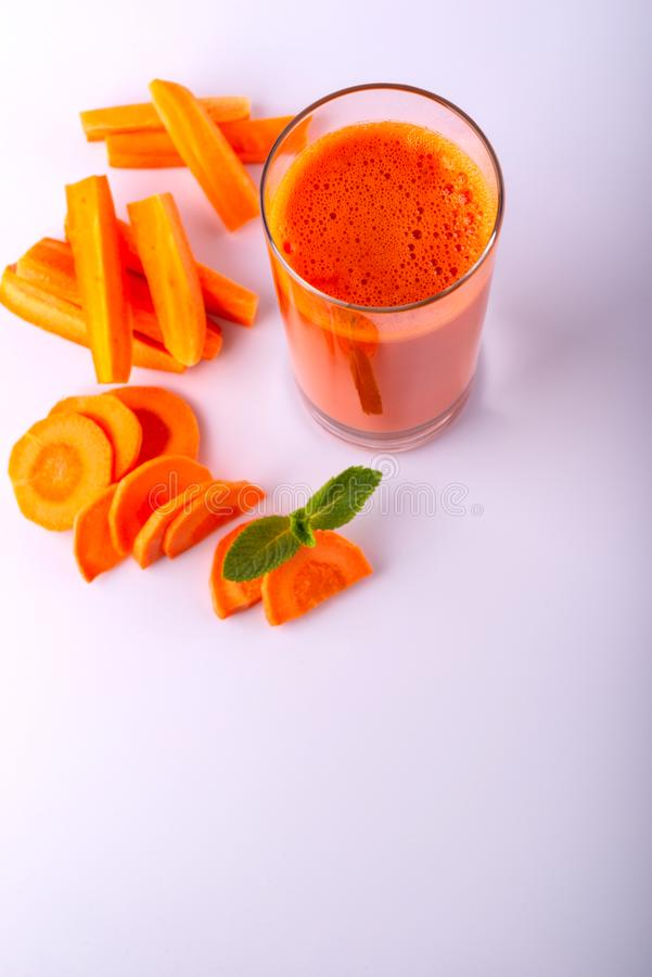 Verre de jus de carotte avec des quelques morceaux de carotte sur un fond blanc Boisson crue de carotte image libre de droits