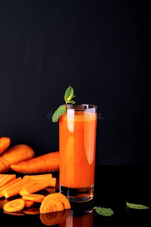 Verre de jus de carotte avec des quelques morceaux de carotte sur un fond noir Boisson crue de carotte photos stock