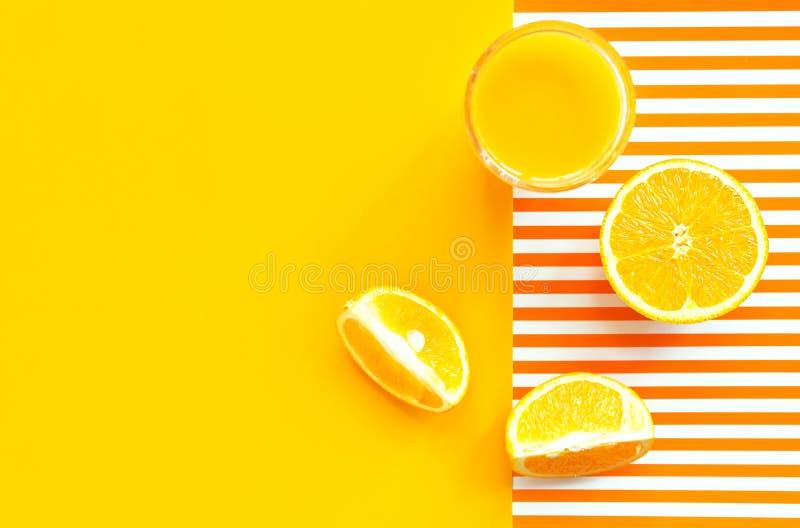 Verre de jus d'orange fra?chement serr? avec la cale de fruit de pulpe sur le fond ray? jaune de duotone et blanc ensoleill? lumi photos stock