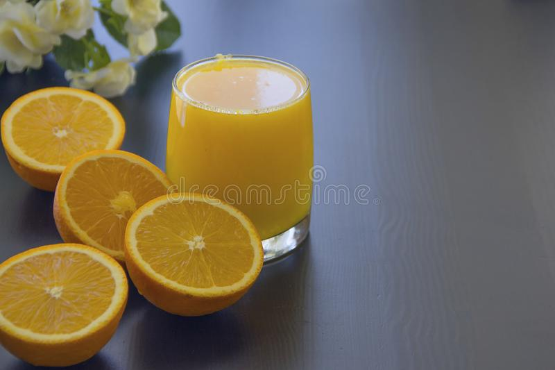 Verre de jus d'orange frais à côté des quatre moitiés des oranges photos stock