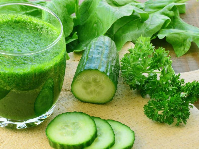Verre de jus de légumes vert avec les légumes frais image stock
