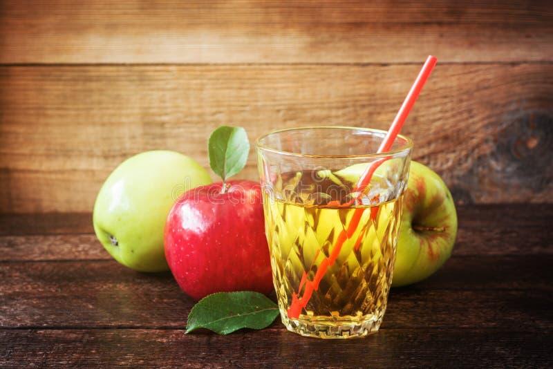 Verre de jus de pomme avec les pommes rouges et vertes sur le fond en bois photographie stock