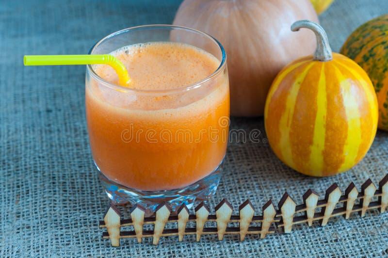 Verre de jus et de quelques uns de carotte savoureux de potiron image stock
