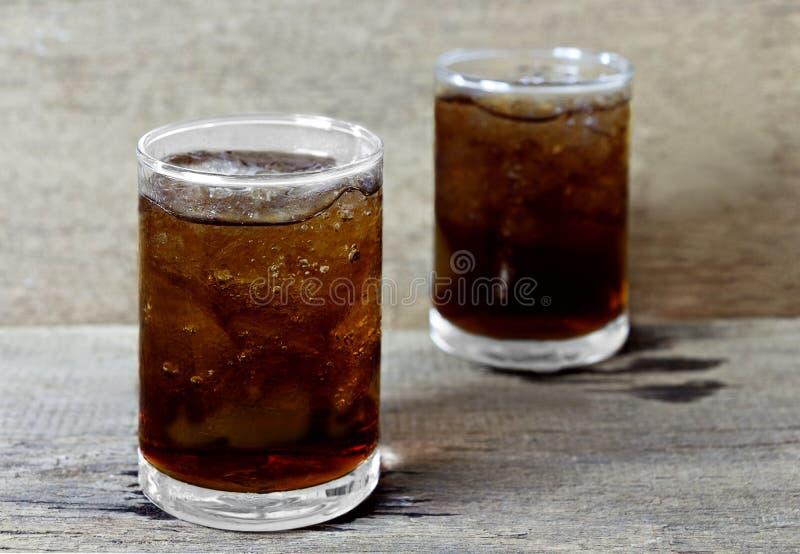 Verre de kola avec de la glace sur la table en bois image libre de droits