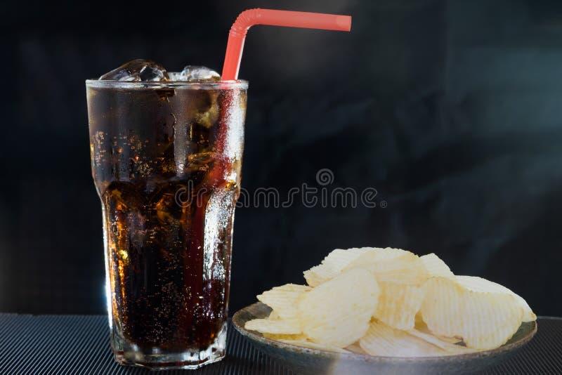 Verre de kola avec des pommes chips sur le fond noir photographie stock