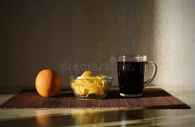 Verre de kola, d'orange et de pommes chips sur la table image libre de droits
