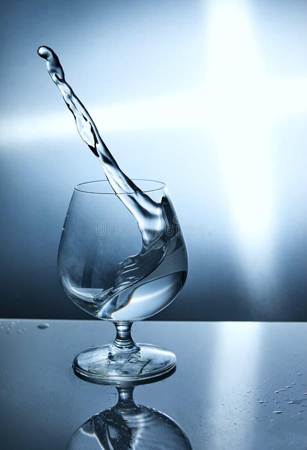 Verre de l'eau avec une vague sur un fond bleu images stock