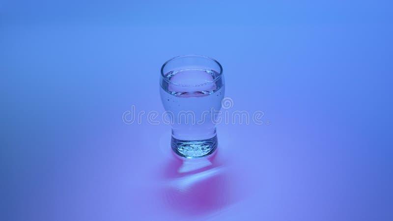 Verre de l'eau sur le fond de couleur image stock
