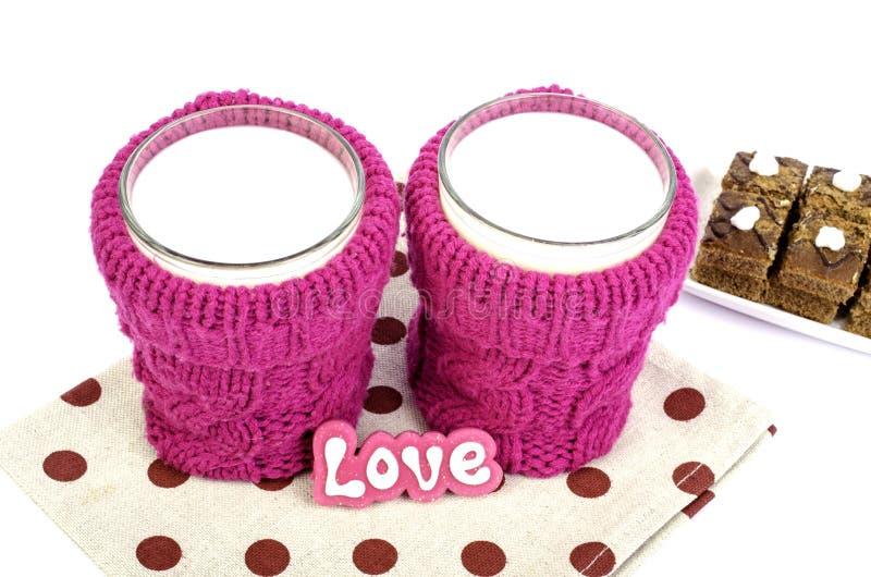 Verre de lait dans un support de tasse tricoté image stock