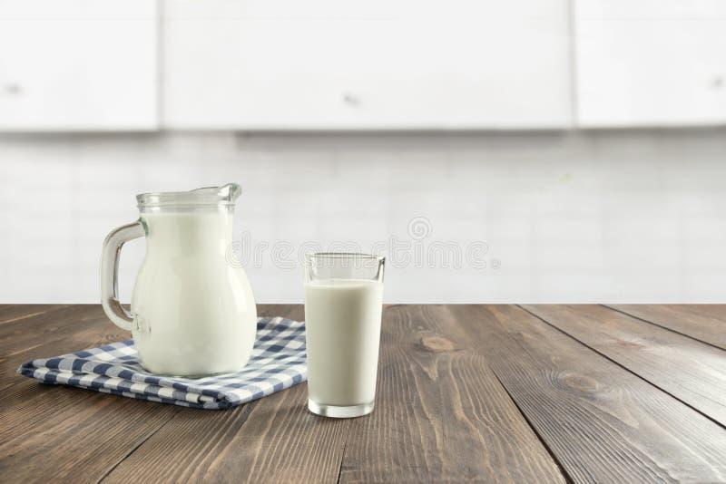 Verre de lait et de cruche frais sur le dessus de table en bois avec la cuisine blanche blured comme fond image libre de droits