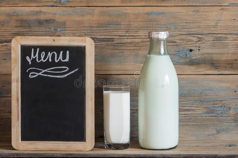 verre de lait sur la table et le tableau noir en bois photo stock