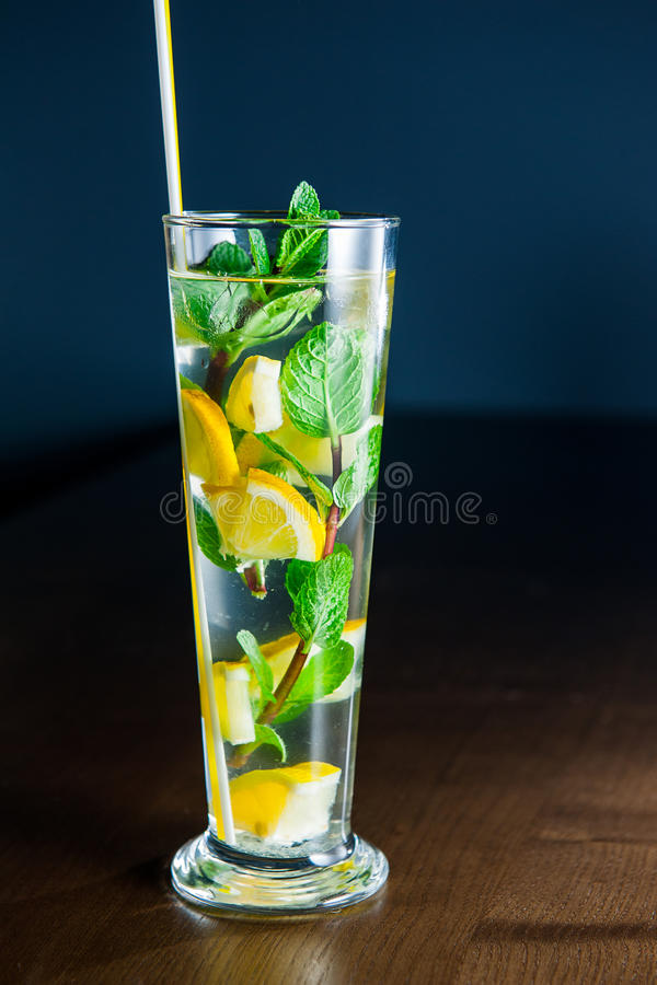 Verre de limonade avec des cales de menthe et de citron sur le fond en bois foncé Foyer sélectif photo stock