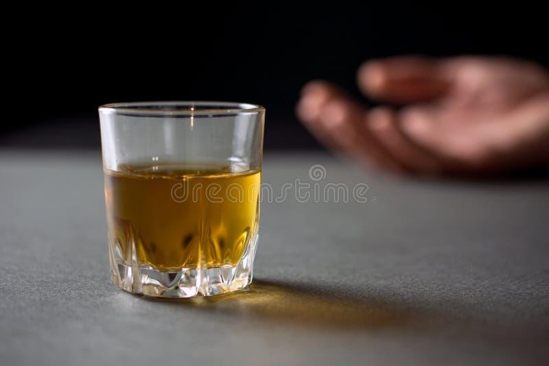 Verre de main de whiskey d'un homme ivre image libre de droits
