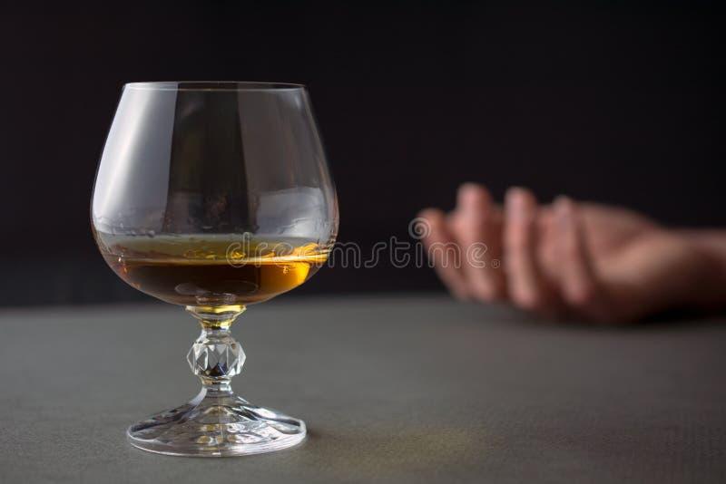 Verre de main de whiskey d'un homme ivre images stock