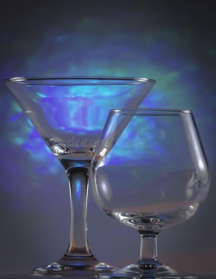 Verre de Martini ainsi que le verre de cognac avec les lumi?res bleues lumineuses de clignotant sur le fond image stock