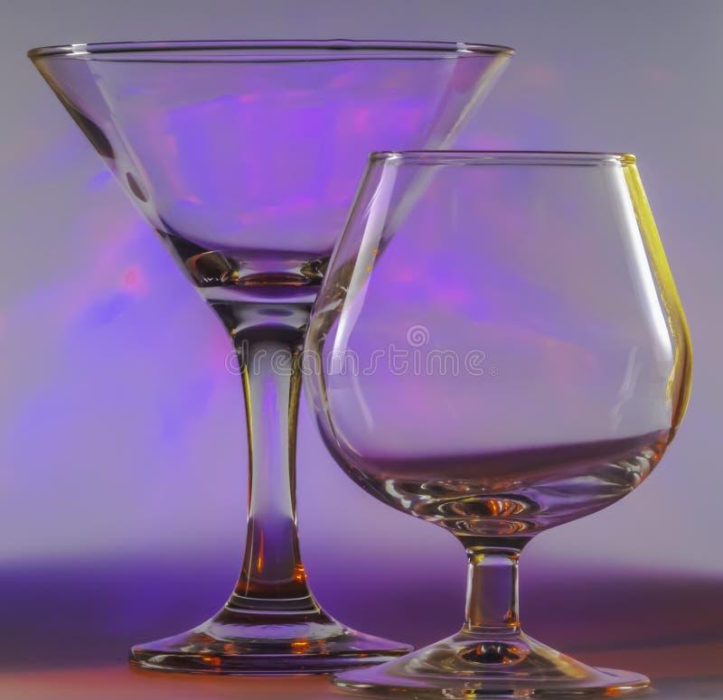 Verre de Martini ainsi que le verre de cognac avec les lumi?res violettes douces de clignotant sur le fond photo libre de droits