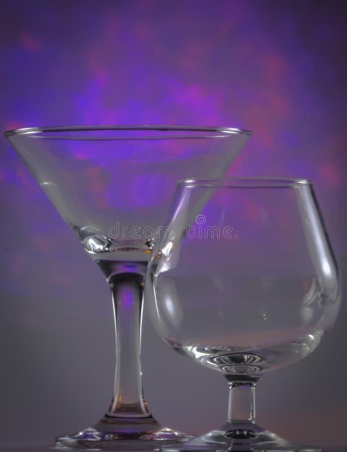 Verre de Martini ainsi que le verre de cognac avec les lumi?res violettes lumineuses de clignotant sur le fond photos stock