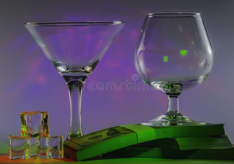 Verre de Martini ainsi que le verre de cognac sur des paquets du 100s de dollars US et glaçons avec les lumières violettes douc photos stock