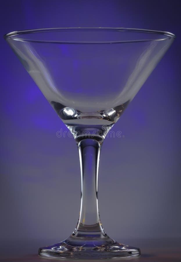 Verre de Martini avec les lumières violettes foncées sur le fond images stock
