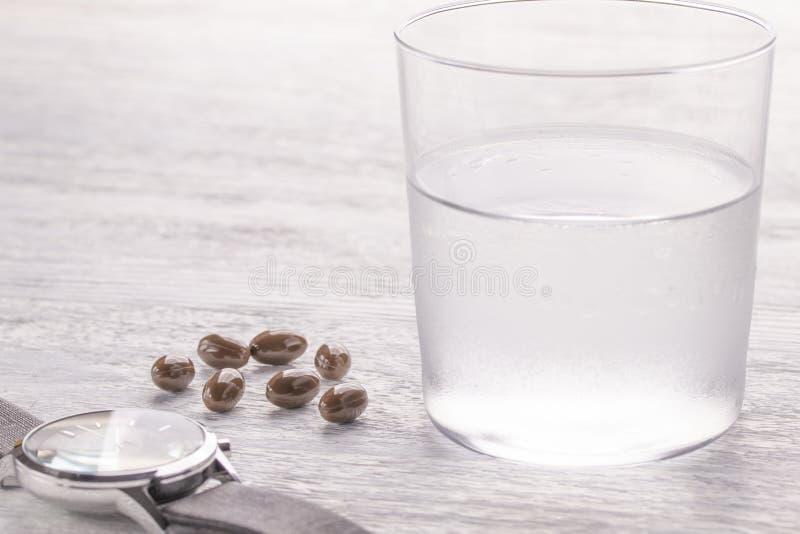 Verre de Misted de l'eau et de capsules médicales brunes sur une vieille table en bois blanche Fermez-vous vers le haut sur un fo photo libre de droits