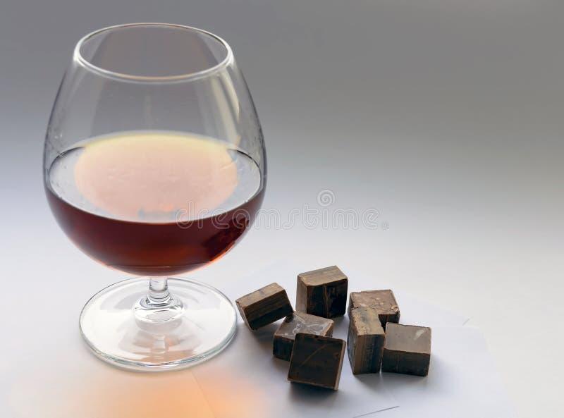 Verre de morceaux d'eau-de-vie fine et de chocolat photographie stock libre de droits