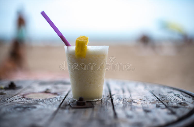 Verre de pinacolada sur la table sur la plage photos stock