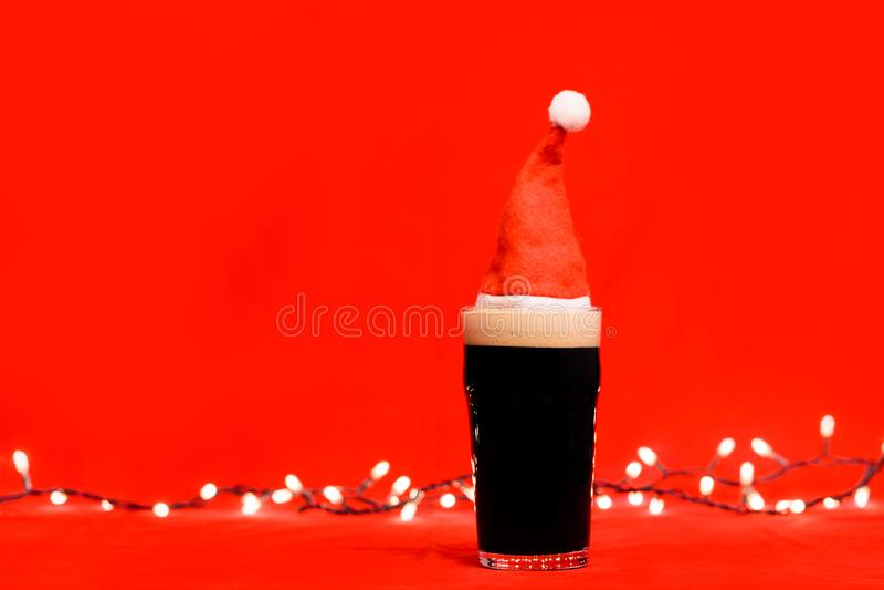 Verre de pinte de bière foncée ou de bière anglaise vaillante avec le chapeau rouge de Santa et les lumières de Noël brouillées à photos libres de droits