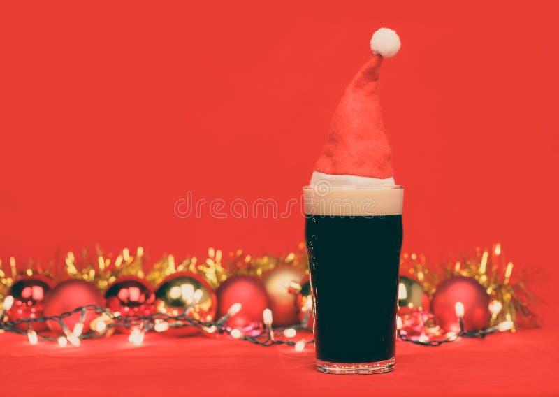 Verre de pinte de bière foncée ou de bière anglaise vaillante avec les babioles et la tresse rouges de lumières de Noël de chapea image libre de droits