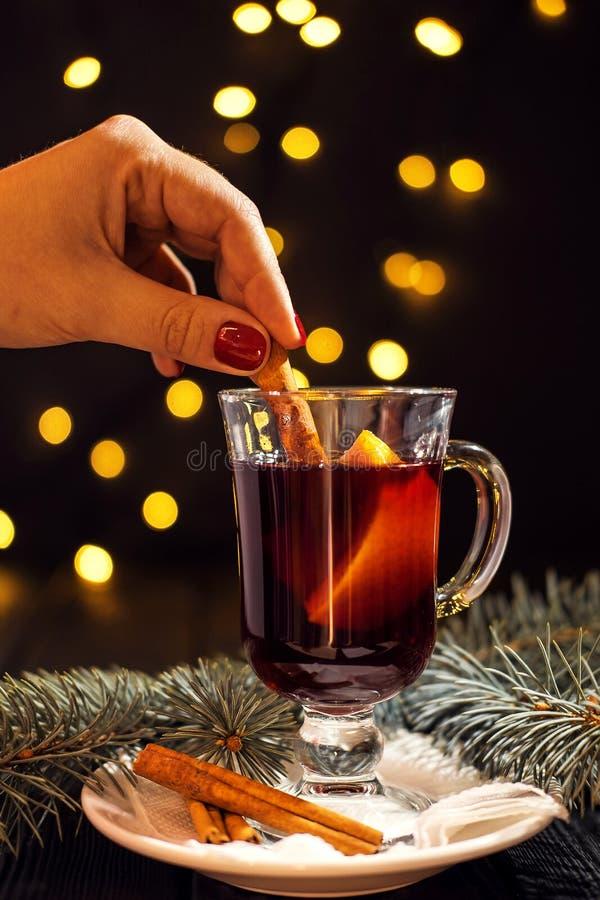 Verre de plan rapproché de vin chaud avec l'orange et la cannelle à disposition de la femme sur le fond noir foncé photo libre de droits