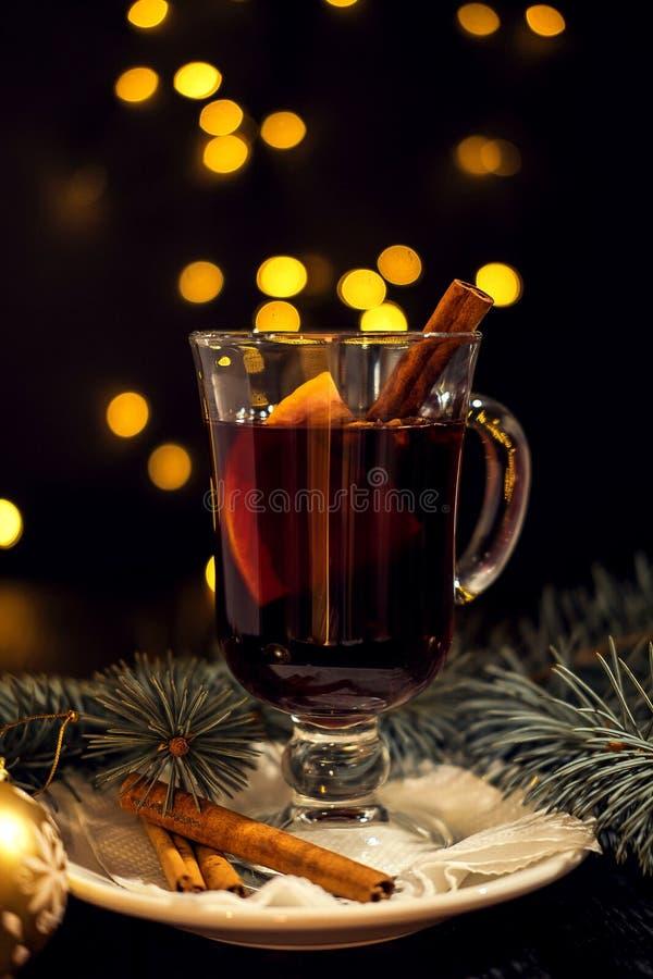Verre de plan rapproché de vin chaud avec l'orange et la cannelle du plat blanc, lumières de Noël images libres de droits