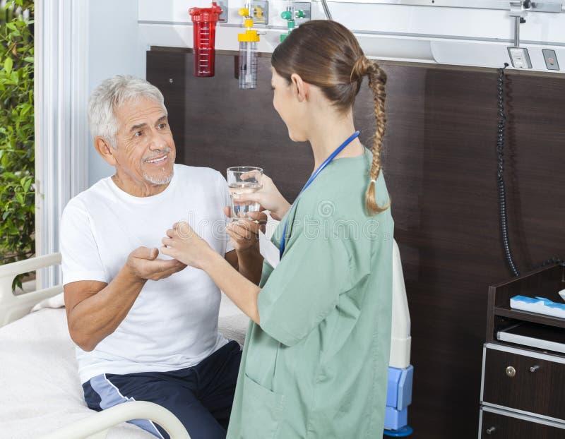 Verre de réception patient heureux de médecine et d'eau d'infirmière photographie stock