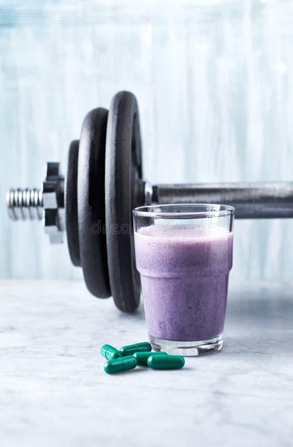 Verre de secousse de protéine avec du lait et des myrtilles, des capsules de L-carnitine et une haltère à l'arrière-plan Nutritio photo stock