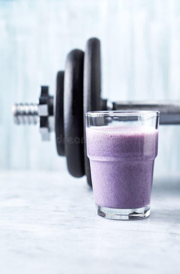 Verre de secousse de protéine avec du lait et des myrtilles et une haltère à l'arrière-plan Nutrition de bodybuilding de sports photo stock