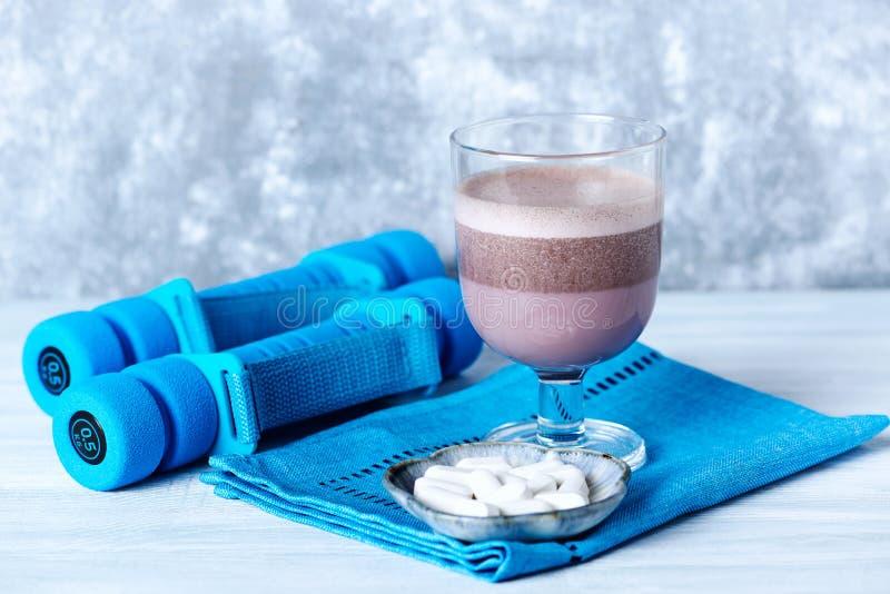 Verre de secousse de protéine de chocolat avec du lait et le cassis L - Carnitine et haltères bleues à l'arrière-plan Nutrition d photographie stock