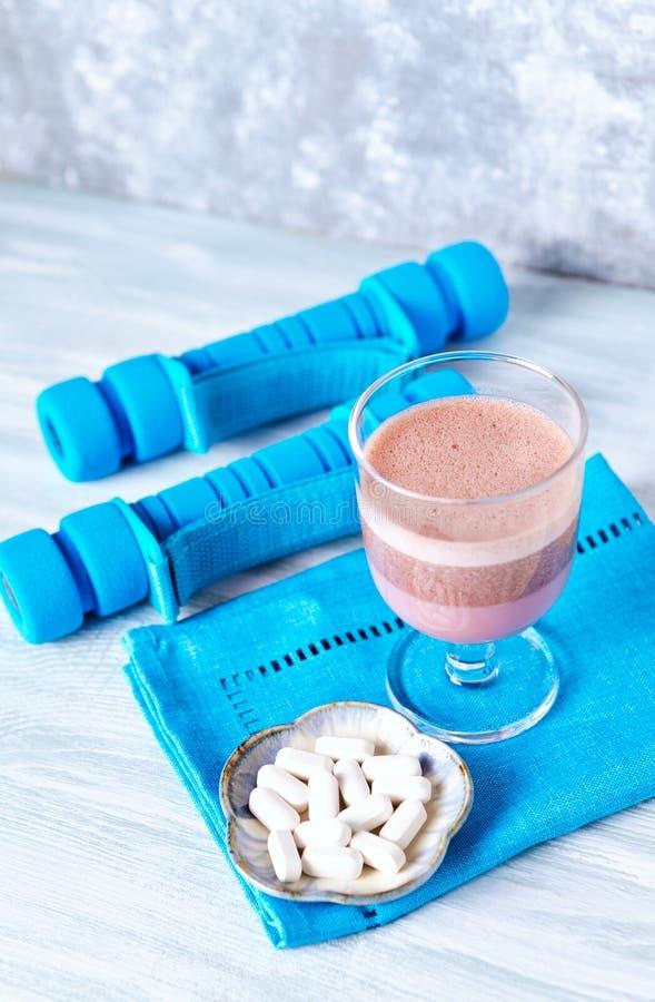 Verre de secousse de protéine de chocolat avec du lait et le cassis L - Carnitine et haltères bleues à l'arrière-plan photos libres de droits